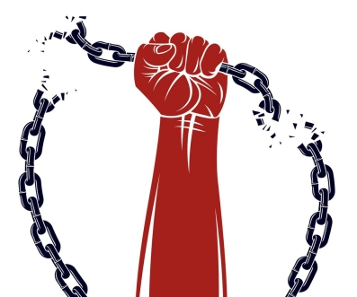 Strong hand clenched fist fighting for freedom against chain sla